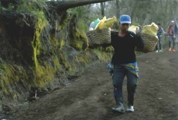 Rudar koji u košarama nosi komade sumpora s dna kratera vulkana Ijen